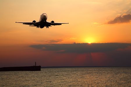 Silhouette of the big plane on a sunset background Stock Photo