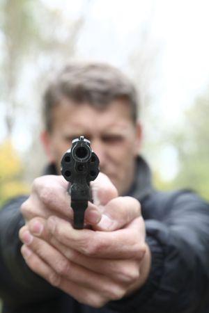 character assassination: man shoots from pistol. Selective focus on pistol barrel.