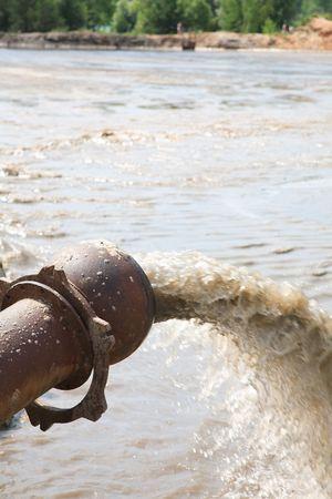 tuberias de agua: Agua sucia fluye de una tuber�a. Desechos t�xicos de producci�n