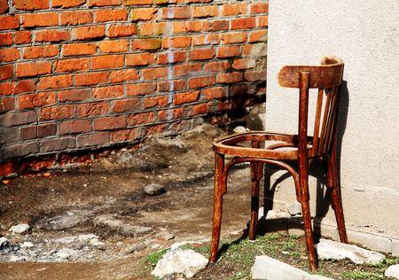 broken chair: old broken chair at brick wall Stock Photo
