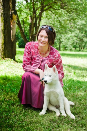 beautiful girl with puppy of husky in park photo