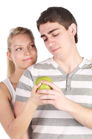girl treats the young man with apple photo