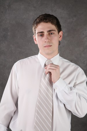 corrects: man corrects a tie against a dark background