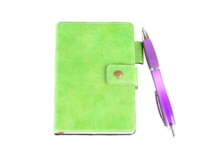 Green notebook and the pen . A white background photo
