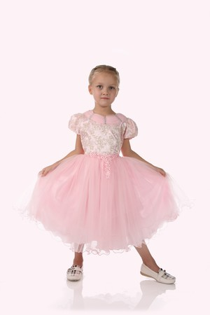 little girl in a pink elegant dress.Pink background photo