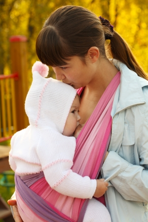 Walk with the child in a baby sling. Breastfeeding photo