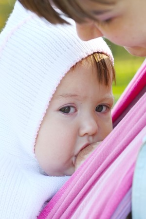 adult offspring: Walk with the child in a baby sling. Breastfeeding Stock Photo