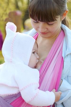 borstvoeding: Lopen met het kind in een baby strop. Borst voeding  Stockfoto