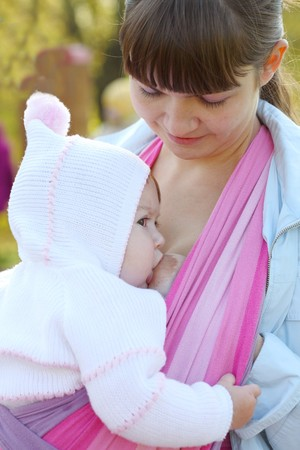 adult breastfeeding: Walk with the child in a baby sling. Breastfeeding Stock Photo