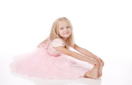 little girl barefoot: little girl in a pink elegant dress.White background