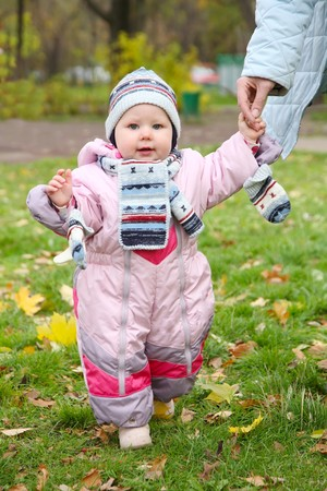 little girl in pink overalls learns to walk photo