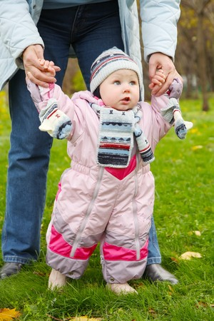 little girl in pink overalls learns to walk Stock Photo - 8270923