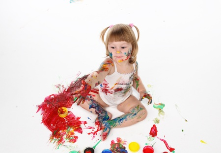 little girl be daubed playing with bright colors