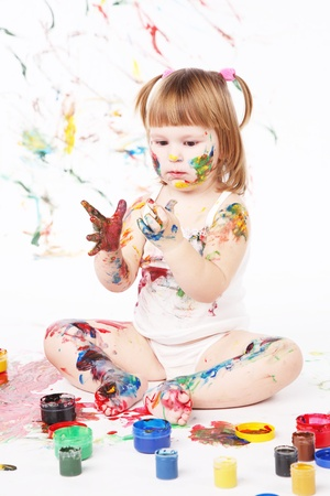 bedaubed: little girl bedaubed playing with bright colors Stock Photo