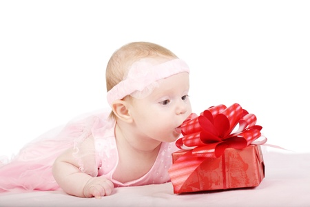 Portrait of the baby - girls in an elegant pink dress with a red gift box photo