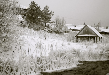 Winter rural landscape with wooden houses and the river photo