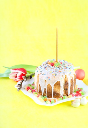 Easter cake with candles on a yellow background. Easter celebrating. photo