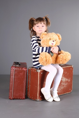 four-year beautiful girl sits on an old suitcase with a toy in hands. Stock Photo - 8888175