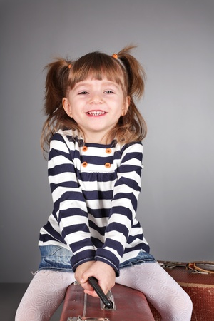 laughing girl: four-year beautiful girl sits on an old suitcase on a gray background