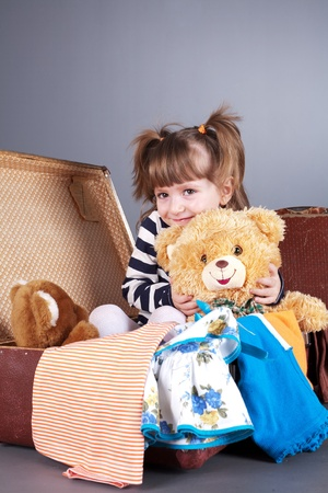 four-year girl joyfully sits in an old suitcase with toys and clothes photo