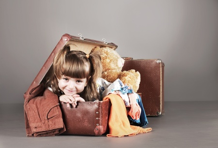 packing suitcase: four-year girl joyfully sits in an old suitcase with toys and clothes