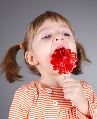 four-year girl with the big sugar candy on a gray background photo