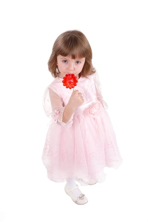 four-year girl in a beautiful pink dress with the big sugar candy. It is isolated on a white background photo