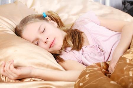 teen girl bedroom: beautiful girl sleeps on silk linen Stock Photo