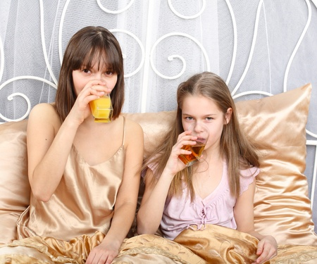 Two sisters drink juice sitting in bed photo