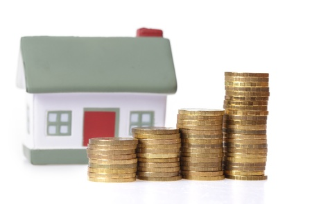 Toy small house and coins in the form of the diagram.  concept of dearness of habitation Stock Photo - 9053348