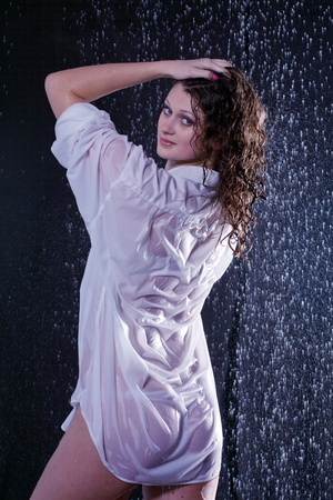 good looking woman: beautiful girl in the rain against a dark background Stock Photo