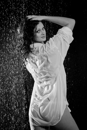 female sexuality: beautiful girl in the rain against a dark background Stock Photo