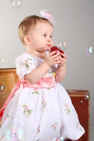 little girl is an apple. A gray background with soap bubbles. photo