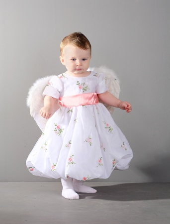 little girl in an elegant dress with wings of an angel on a gray background. photo