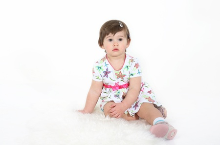 sheep skin: little girl sits on a white sheep skin