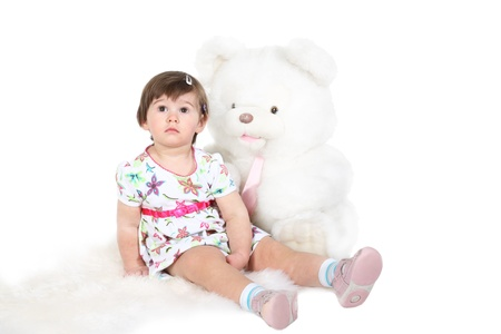 sheep skin: little girl sits on a white sheep skin with the big toy bear