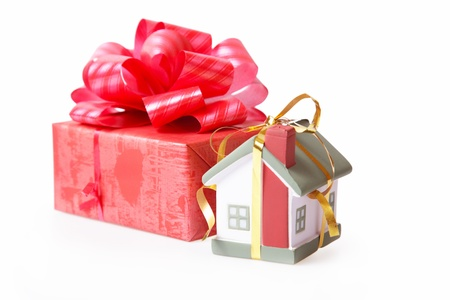 Habitation in a gift. A toy small house and a red gift box. photo