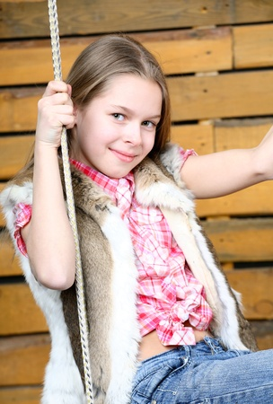 ten years girl shakes on a swing photo