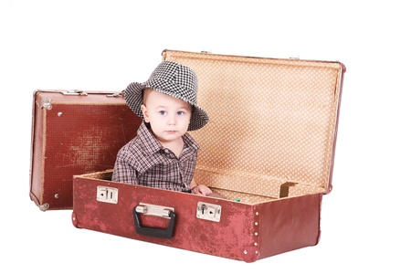 little boy sits in an old suitcase photo