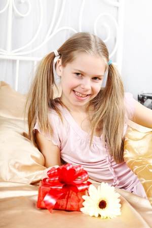 little girl smiling: beautiful ten years girl has seen in bed a gift on birthday.