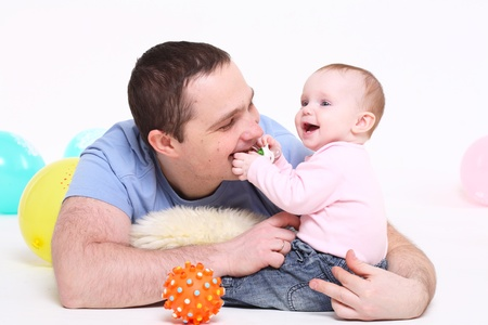 baby's dummies: father plays with the eight-monthly daughter. It is isolated on a white background.