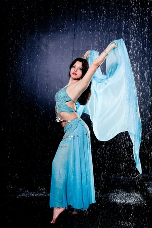 girl executes east dance in the rain against a dark background photo