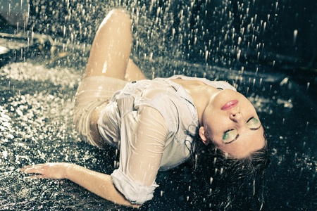 beautiful girl in the rain against a dark background photo