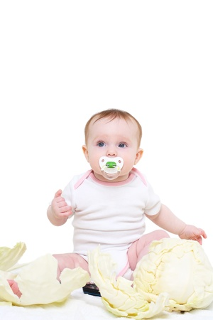 baby's dummies: eight-monthly baby sits in cabbage leaves