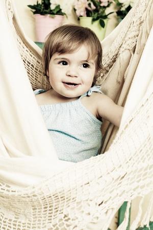 little girl shakes in a soft hammock photo
