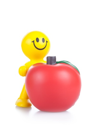 petit bonhomme: smiling toy little man with the big red apple. It is isolated on a white background Banque d'images