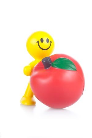 the little man: sorridente piccolo uomo giocattolo con la grande mela rossa. Si � isolato su uno sfondo bianco Archivio Fotografico