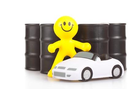 the little man: giocattolo sorridente piccolo uomo contro mozziconi con i costi del petrolio vicino alla macchina.