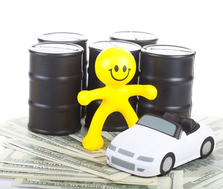 the little man: giocattolo sorridente piccolo uomo contro mozziconi con i costi del petrolio vicino alla macchina su una notevole quantit� di denaro. Il concetto di acquisto e vendita di carburante.