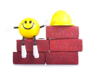 the little man: Un sorridente piccolo uomo giocattolo vicino ad un mucchio di mattoni. La costruzione concetto.